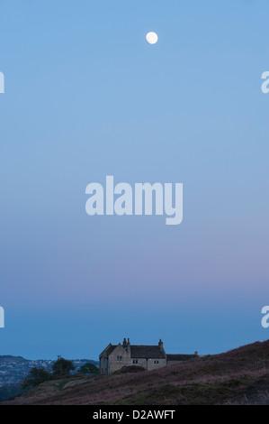 Pleine lune au crépuscule, haut dans un ciel bleu au-dessus sur une maison en pierre sur la lande de bruyère - au Banque D'Images