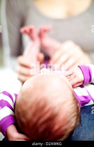 Tout petit bébé nouveau-né allongé sur ses genoux les mères avec sa tête vers l'appareil photo avec les 6 Banque D'Images