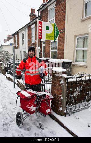 Royal Mail postman offre mail en temps d'hiver enneigé. Reading, Berkshire, Angleterre, Royaume-Uni. Banque D'Images