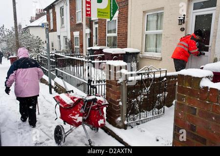 Royal Mail postman offre mail en temps d'hiver neigeux, tandis qu'une femme âgée, escaliers à travers la glace aux Banque D'Images