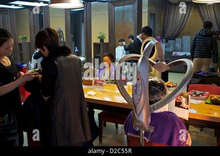 Dames chinoises obtenir leurs cheveux traitement à un salon de coiffure à Beijing, Chine.12-Jan-2013 Banque D'Images