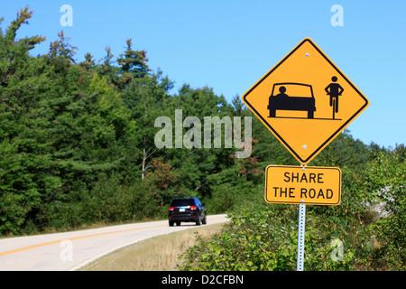 Un partage de la route avec les vélos jaune Attention à côté d'une autoroute Banque D'Images