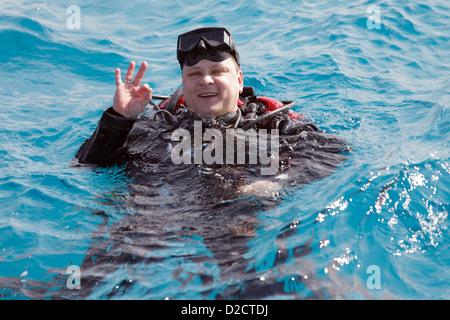 Un plongeur montrant le signal OK sur la surface de l'eau. Banque D'Images