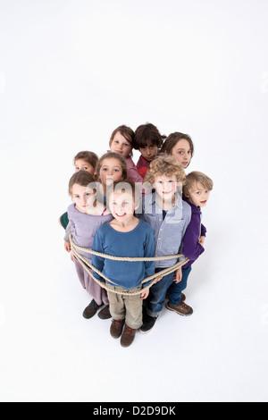 Un groupe d'enfants attachés ensemble par une corde Banque D'Images