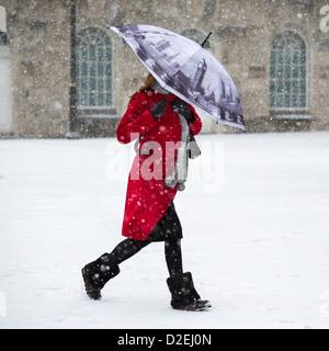 Une femme marche dans la neige à Victoria Square, Birmingham, UK. Le cadre décrit les Chambres du Parlement à Londres.
