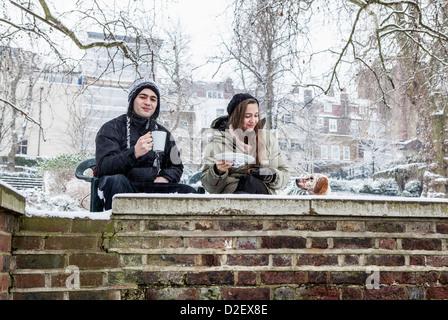 Jeune femme, l'homme et le chien appréciant une boisson chaude sur les rives de la Tamise que la neige tombe en Banque D'Images
