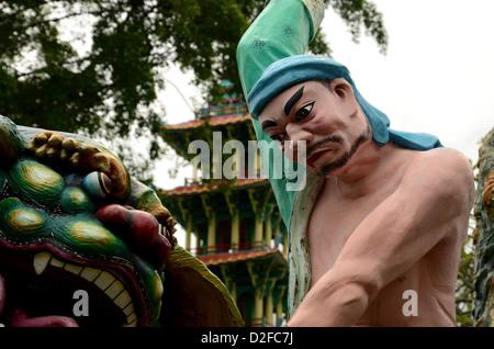 La statue d'un torse nu chinois avec turban bleu s'attaquer à un animal. L'animal est un lion gardien mythique ou Banque D'Images