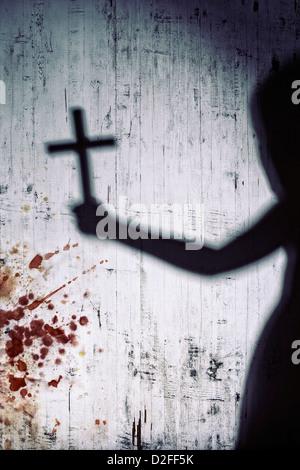 Ombre d'une personne avec une croix sur un mur blanc sanglante Banque D'Images