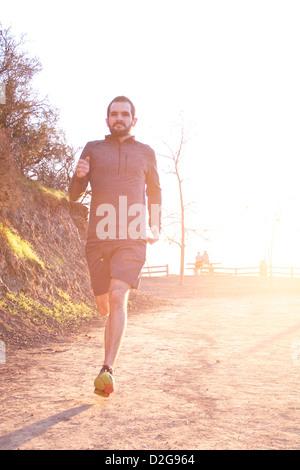 Un homme jouit d'un sentier à travers Griffith Park à Los Angeles, alors que le soleil se couche derrière lui Banque D'Images