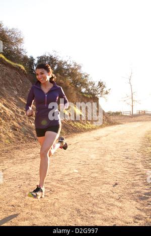 Une femme prendre un trail courir à travers Griffith Park à Los Angeles, alors que le soleil se couche derrière Banque D'Images