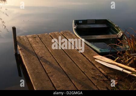 Jetée en bois pier par Lakeside en fin d'après-midi la lumière avec bateau à rames et avirons en bois Banque D'Images