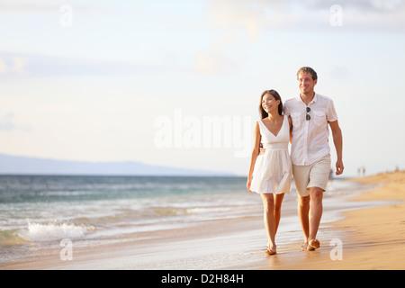 Les jeunes professionnels l'interracial couple walking on beach Banque D'Images