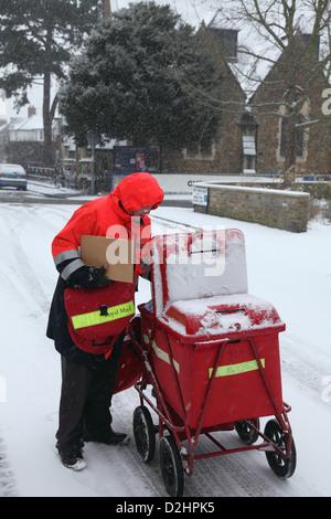 Facteur distribue le courrier à Londres en janvier une chute de neige. Banque D'Images