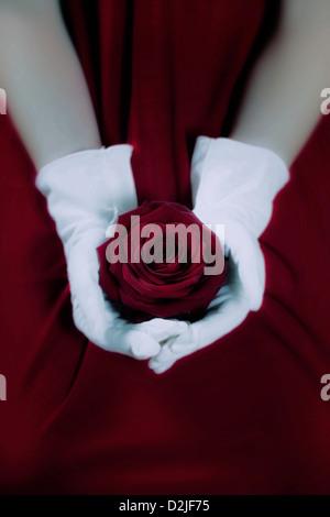 Une femme dans une robe rouge avec des gants blancs tient une rose rouge sur ses genoux Banque D'Images