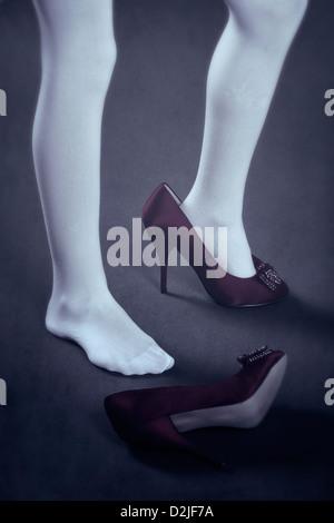 Une fille en bas blancs avec des chaussures trop grande Banque D'Images