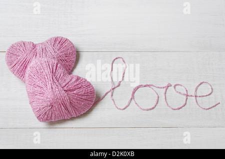 Deux clews rose en forme de coeur avec mot amour obtenus à partir de fils sur fond de bois blanc Banque D'Images