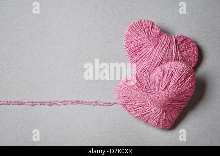 Forme de coeur rose faite de laine sur fond gris Banque D'Images
