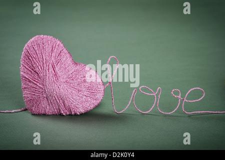 Clew rose en forme de coeur avec mot amour obtenus à partir de fils sur fond vert Banque D'Images