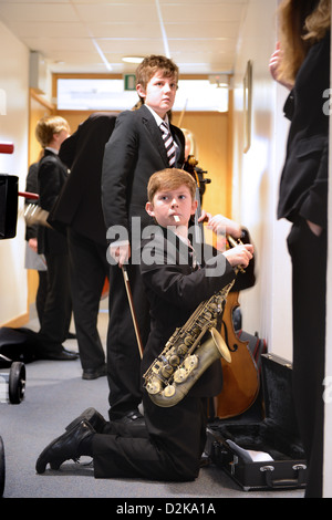 Un garçon avec son saxophone avant un concert à Pates Grammar School à Cheltenham, Gloucestershire UK Banque D'Images