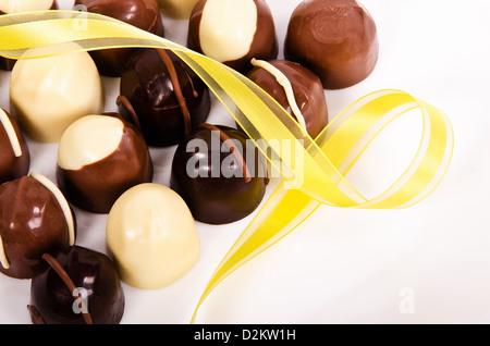 Assortiment de bonbons au chocolat foncé et blanc avec ruban jaune Banque D'Images