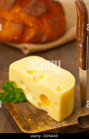 Morceau de fromage Edam bio frais sur planche de bois avec du pain frais sur la table de cuisine petit déjeuner Banque D'Images