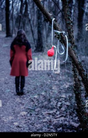 Un vieux ballon rouge suspendu à une branche, à une distance d'une femme dans un manteau rouge Banque D'Images