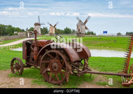 Vieux tracteur et moulins à vent. L'Estonie Banque D'Images