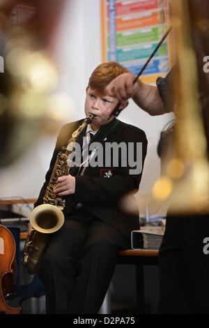 Un garçon jouant un saxaphone lors d'une pratique de la bande à Pates Grammar School à Cheltenham, Gloucestershire Banque D'Images