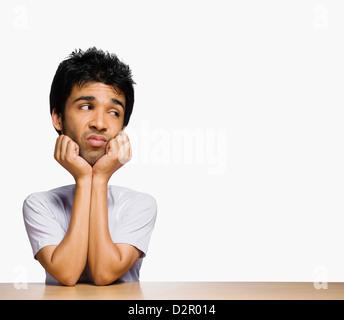 Homme triste à côté avec ses mains sur le menton Banque D'Images