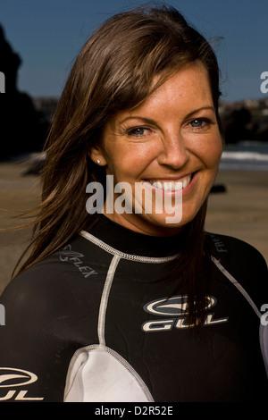 Portrait of female surfer en combinaison, smiling Banque D'Images