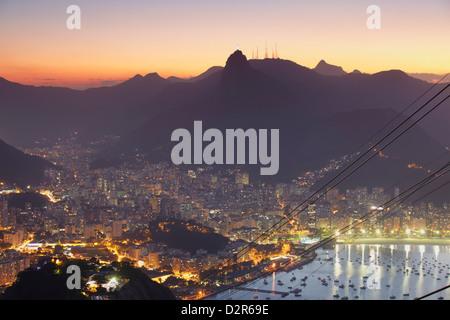 Vue sur le Christ Rédempteur statue et Botafogo Bay au coucher du soleil du mont du Pain de Sucre, Rio de Janeiro, Banque D'Images