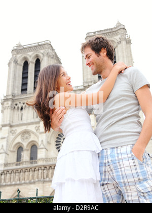 Happy young couple in front of Notre Dame de Paris, France. Asian Woman and Caucasian man Banque D'Images