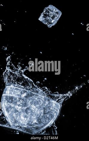 Cube de glace tomber à l'eau dans le verre, energy drink Banque D'Images