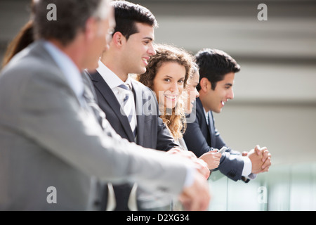 Portrait of confident businesswoman standing with co-workers in a row Banque D'Images