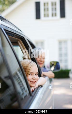 Femme plus âgée et petite-fille leaning out car windows Banque D'Images