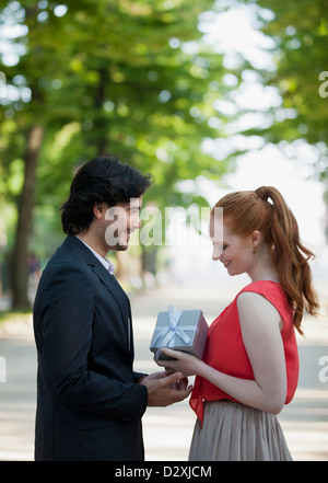 Man giving woman gift in park Banque D'Images