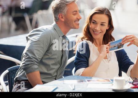 Smiling couple avec postcard at sidewalk cafe Banque D'Images