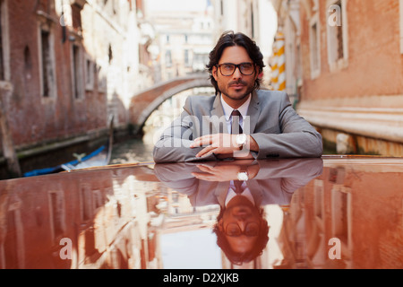 Portrait of serious businessman riding boat in canal à Venise Banque D'Images