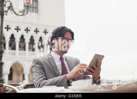 Businessman using digital tablet at sidewalk cafe à Venise Banque D'Images