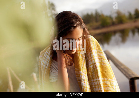 Smiling woman wrapped in blanket at lakeside Banque D'Images