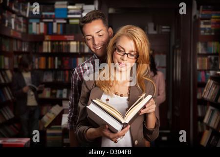 Close-up of attractive young couple dans une bibliothèque pour lire un livre avec d'autres personnes et des étagères Banque D'Images