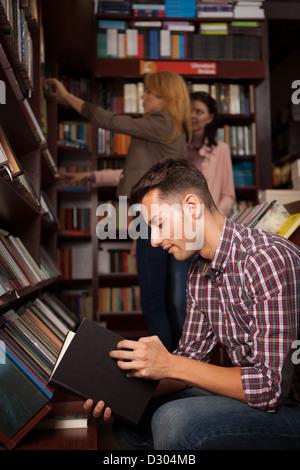Young caucasian beau mec dans une librairie pour lire un livre avec d'autres personnes en arrière-plan Banque D'Images