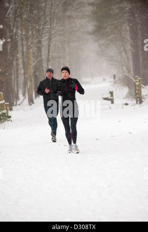 Couple running through fortes chutes de neige dans un Park, Royaume-Uni Banque D'Images