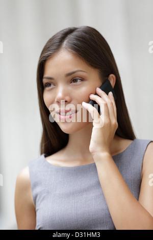 Belle jeune québecoise / multiraciale chinois asiatique professional Woman talking on smartphone à l'extérieur Banque D'Images