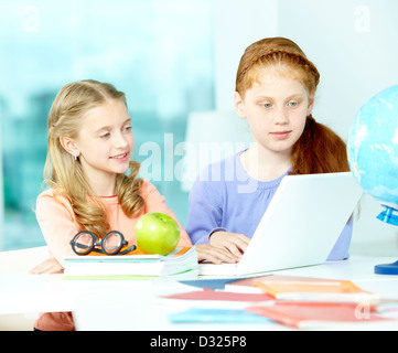 Portrait d'écolières smart assis en classe à l'avant de l'ordinateur portable Banque D'Images