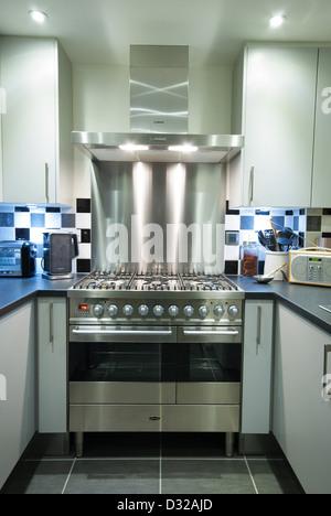 Un gaz moderne + électrique cuisinière avec hotte et refoulement dans une petite cuisine contemporaine. UK, 2013. Banque D'Images