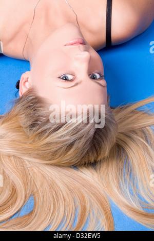 Une belle jeune femme portant un regard en arrière vers la caméra en studio sur fond bleu Banque D'Images