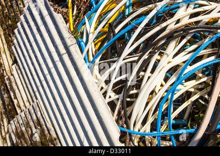 L'amiante déposés illégalement de draps avec gaine de câble en plastique laissés par metal theives qui a volé le Banque D'Images