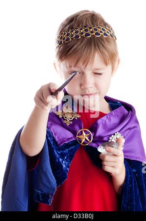 Petit garçon qui prétend être le roi assistant jette sort avec baguette magique. Banque D'Images