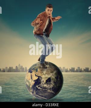 Jeune homme en équilibre sur une planète terre Banque D'Images